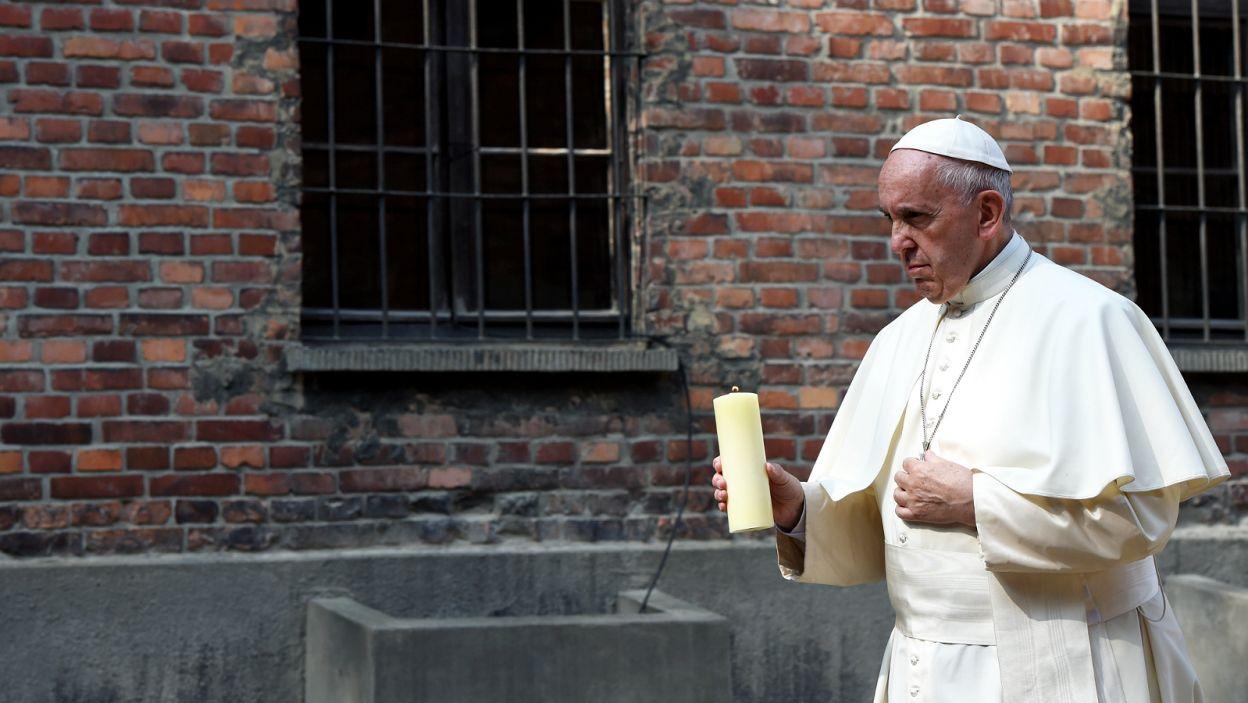 Papież zmierza z zapaloną świecą do Ściany Śmierci, gdzie naziści rozstrzeliwali więźniów (fot. PAP)