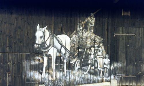 Kuźmina, wieś w gminie Bircza na Podkarpaciu. Leży na Pogórzu Przemyskim. Do 1954 istniała gmina Kuźmina.  Mural inspirowany fotografią z sąsiedniego Rozpucia, przedstawiającego Pana Filika z rodziną.Fot. Arkadiusz Andrejkow