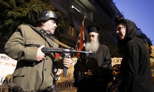 Rekonstrukcja nazistowskiej zbrodni wojennej w Distomo, podzas protestu przed ambasadą Niemiec w Atenach6 października 2011 r. Człowiek odgrywający niemieckiego żołnierza grozi Greczynce, jej dziecku i duchownemu. Demonstranci, pod przewodnictwem greckiego filmowca Dimitrisa Kollatosa, wystawili spektakl w proteście przeciwko roli Niemiec w kryzysie finansowym panującym w Grecji. Fot. REUTERS / Yiorgos Karahalis
